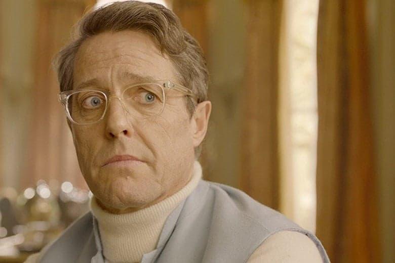 Hugh Grant em Paddington 2, usando óculos e com cabelo grisalho